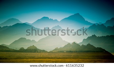 A beautiful, colorful, abstract mountain landscape with a hot summer haze in warm green tonality. Decorative, artistic double exposure. #611635232
