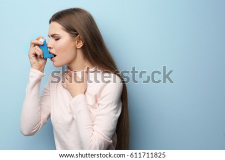 Young woman using asthma inhaler on color background Royalty-Free Stock Photo #611711825