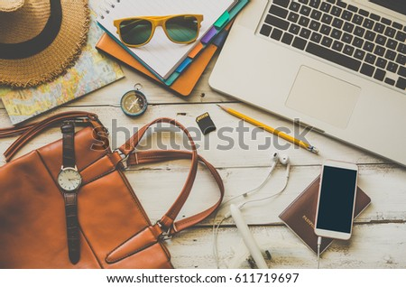 Laptop and travel accessories costumes Tourism planning and equipment needed for the trip on wooden floor #611719697