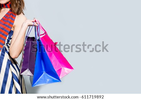 Young happy summer shopping woman with shopping bags isolated on grey background #611719892