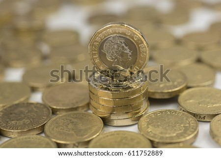 New British one pound sterling coin alongside the old one pound coins up close macro studio shot against a shiny reflective White background #611752889