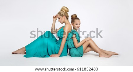 Stunning beauty a young mother with a cute blonde daughter sitting on a white background dressed in a  spring clothings #611852480