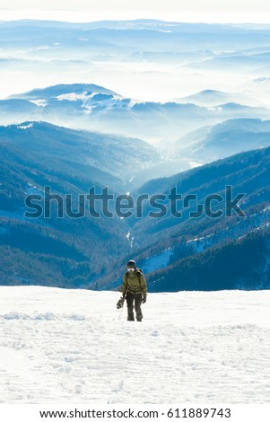 Snowboarder heading towards top of a mountain with beautiful scenery behind his back #611889743
