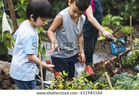 Group of kindergarten kids learning gardening outdoors #611985584