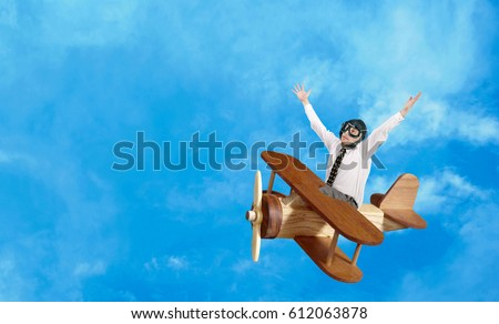 Happy businessman aviator flies in a toy wooden plane against a blue cloudy sky. Successful business #612063878