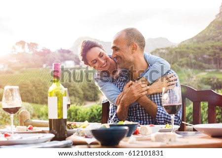Happy mature couple looking at each other while hugging after lunch. Smiling couple in love sitting at dining table. Happy woman embracing from behind her boyfriend outdoor. #612101831