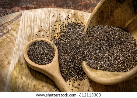 Wooden bowl on wooden board with chia seeds #612113303