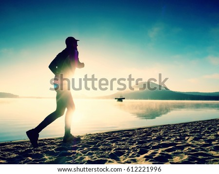 Silhouette of sport active man running on the lake beach at sunrise. Healthy lifestyle. Alone young fitness man exercise  at morning beach #612221996