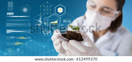 science, biology, ecology and research concept - close up of young female scientist wearing protective mask holding petri dish with plant and soil sample over blue background and virtual charts Royalty-Free Stock Photo #612499370