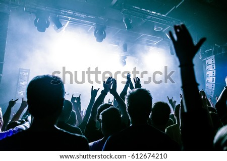 Silhouettes of people in a bright in the pop rock concert in front of the stage. Hands with gesture Horns. That rocks. Party in a club. Sold out. #612674210