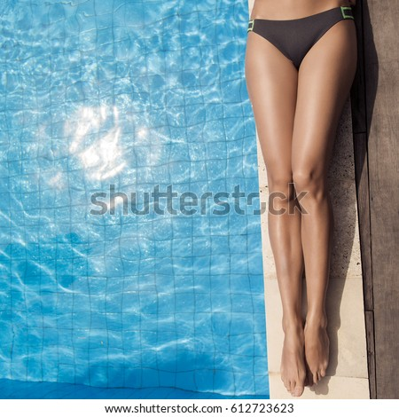 Beautiful woman legs sunbathing near swimming pool. #612723623
