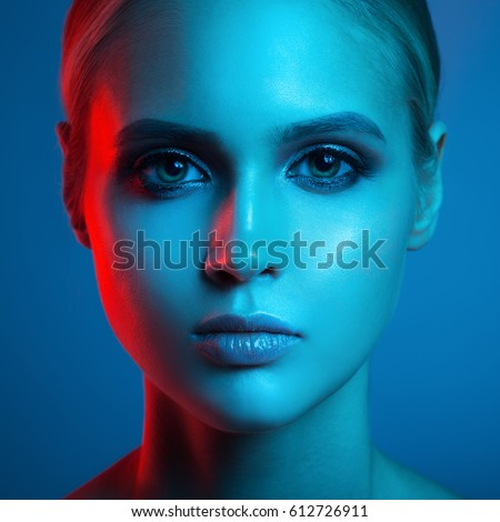 Fashion art portrait of beautiful woman face. Red and blue light color. #612726911