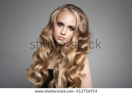 Portrait Of A Beautiful Young Blond Woman With Long Wavy Hair #612726914