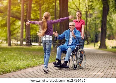 disabled grandfather in wheelchair welcoming his happy granddaughter Royalty-Free Stock Photo #612736436