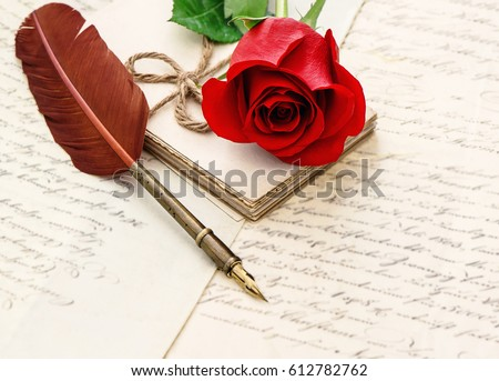 Red rose flower, old letters and antique feather pen. Vintage style background. Undefined blurred text. Selective focus