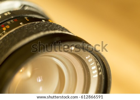 Donetsk,Ukraine - 31 March 2017. Photography gear on the yellow wooden floor. Chinon wide prime lens close up. Photographer equipment in the light of sunset indoors. #612866591