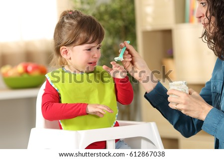 Toddler crying at lunch time sitting in a highchair in the living room at home with a homey background #612867038