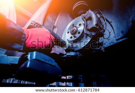 Cleaning disc brake on car, in process of new tire replacement. Car brake repairing in garage Royalty-Free Stock Photo #612871784