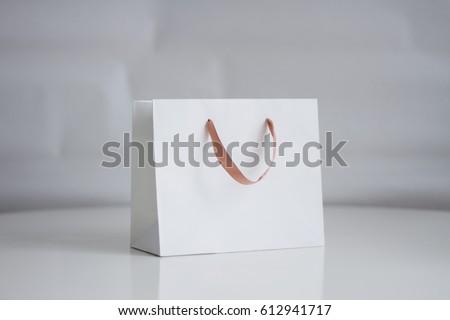 Mock-up of white shopping bag on neutral background Royalty-Free Stock Photo #612941717