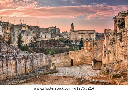 Gravina in Puglia, Bari, Italy: landscape at sunrise of the old town with the cathedral seen from the pathway with the source at the entrance of the ancient aqueduct bridge over the ravine