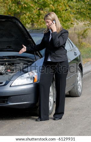 Businesswoman Broken Down By The Side Of The Road With A Stalled Car, Calling For Help On A Cellphone #6129931