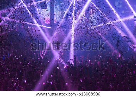 Light Show And Silhouette hands of audience crowd people use smart phones enjoying the club party with concert.  Blurry night club DJ party people enjoy of music dancing sound.Abstract Background. Royalty-Free Stock Photo #613008506