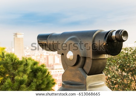 Touristic telescope and blurred city on background. Old metal binoculars on background viewpoint. Barcelona, Spain. #613068665