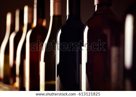 Bottles of old aged wine collection in a row in winery cellar #613121825