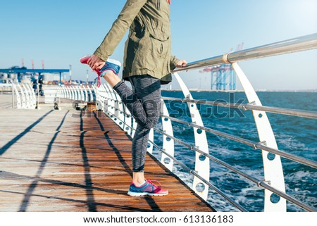Sporty woman in a jacket and sneakers is stretching her legs on the beach in the morning. Concept of a healthy lifestyle. #613136183