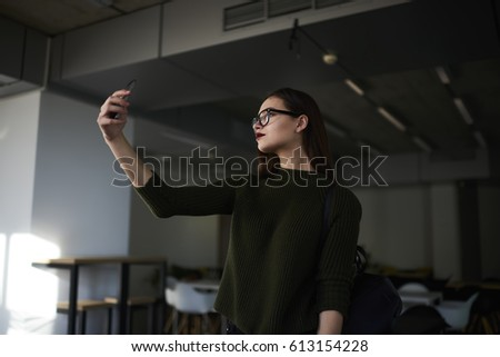 Attractive young student girl after hard exam preparation in university library making serious selfie for more likes in social network on modern smartphone using free wifi connection in campus