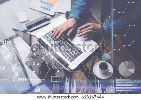 Man working at sunny office on laptop while sitting at the wooden table.Concept of digital screen,virtual worldwide connection icon,diagram,graph interfaces on background.Blurred,visual effects
