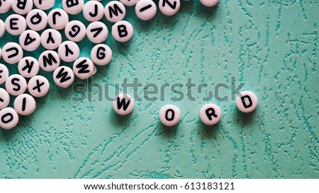 Word word made of round plastic blocks on the table mint color.
