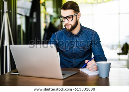 Student taking notes down from his new laptop computer while browsing the internet with his morning coffee #613301888