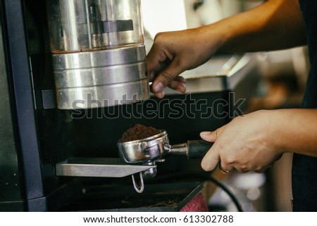Closeup of woman's hand taking ground coffee from coffee-grinder #613302788