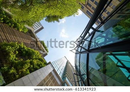 Low angle shot of modern glass buildings and green with clear sky background. #613341923