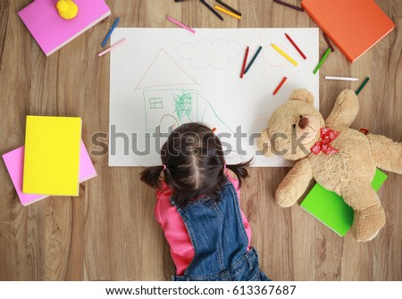 Little Asian girl drawing with color pen in paper on floor at home, Baby healthy and preschool concept