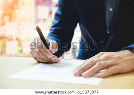 Close-up Of Businessperson Signing Contract,woman writing paper at the desk with pen and reading books at table with basic business Form document working in office #613375877