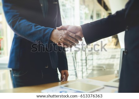 Business partnership meeting concept. Image business people shaking hands while sitting at the working place. Successful businessmen handshaking after good deal. Horizontal, #613376363