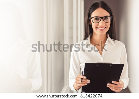 Beautiful young psychotherapist is holding a folder, looking at camera and smiling while standing in office Royalty-Free Stock Photo #613422074