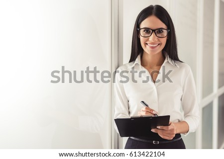 Beautiful young psychotherapist is making notes, looking at camera and smiling while standing in office Royalty-Free Stock Photo #613422104