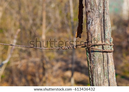 Wooden fence made of wooden sticks and barbed wire. Various textures #613436432