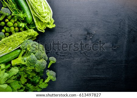 Collection of fresh green vegetables placed on black stone #613497827