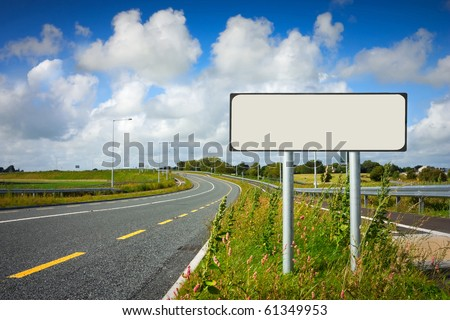 road with sign pole and blue sky with clouds