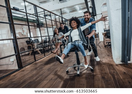 We are the winners!  Four young cheerful business people in smart casual wear having fun while racing on office chairs and smiling Royalty-Free Stock Photo #613503665