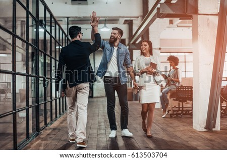 High-five!  Full length of two cheerful young business people giving high-five while their colleague looking at them and smiling Royalty-Free Stock Photo #613503704
