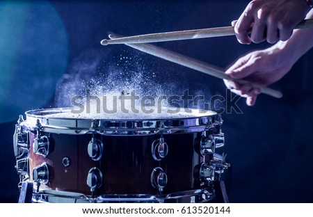 man plays musical percussion instrument with sticks closeup on a black background, a musical concept with the working drum, beautiful lighting on the stage #613520144