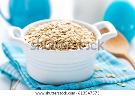 Rolled oats on white wooden background #613547573