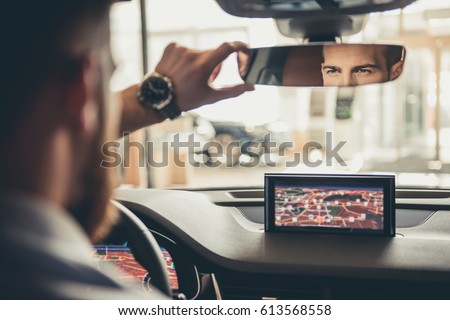 Handsome bearded businessman is looking into the rear view mirror while driving the car Royalty-Free Stock Photo #613568558