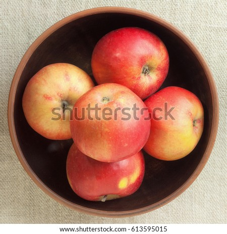 Red apples on a brown background in a bowl . #613595015