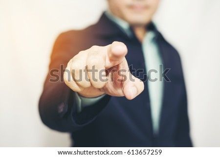 Business man pointing finger soft focus background Royalty-Free Stock Photo #613657259